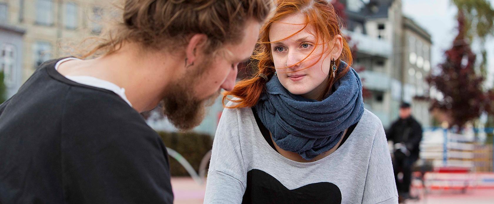 En ung mand og kvinde taler sammen